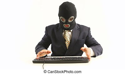 hacker in office - guy in official suit and balaclava typing...