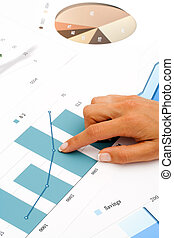 Female hand pointing at financial graphics.