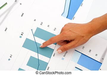Female hand pointing on business graphics.