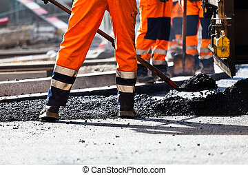 Road construction, worker with shovel - Workers on a road...