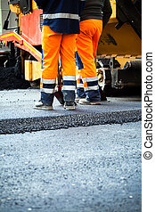 Road construction, teamwork - Workers on a road...
