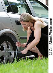 Woman changing a car tyre