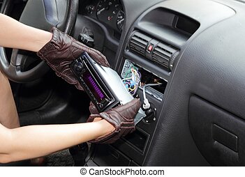Thief stealing a car radio - Gloved hands of a thief...