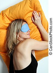 Woman sleeping in a mask - Exhausted attractive blonde woman...