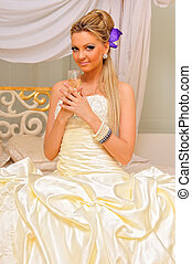 The bride with glass of champagne in the luxuriant inteior -...