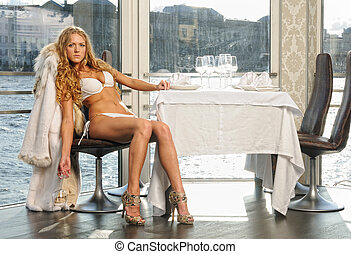 beautiful blonde woman in a restaurant at the water