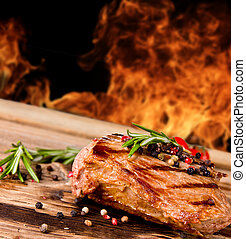 Steak - Grilled beef steak with flames on background