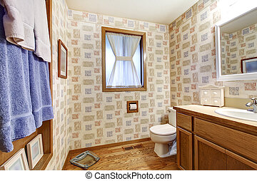 Old brown bathroom with wallpaper and blue towels.