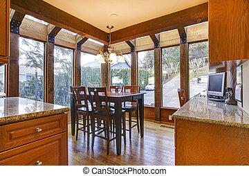 Breakfast room near kitchen with many narrow windows.
