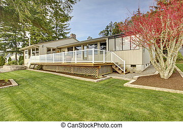Beige one story house with deck and grass during spring. -...