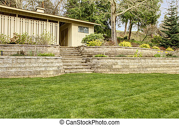 Retaining brick with steps wall with garage building. -...