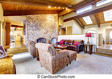 Living room wtih wood ceiling with brick fireplace.