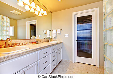 Large bathroom with white cabinets and glass shower.
