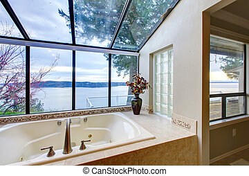 Large tub with glass wall with water view.
