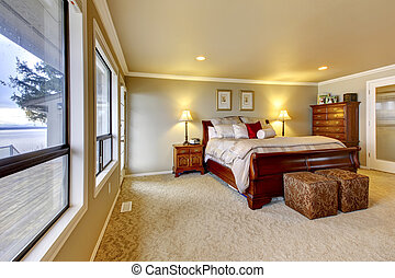 Master bedroom wtih beige walls and wood bed - Large bedroom...