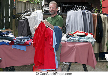 Man at a Tag Sale - Handsome middle age man holding shirts...