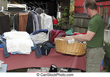 Mature Man at a Garage Sale - Male holding a basket with...