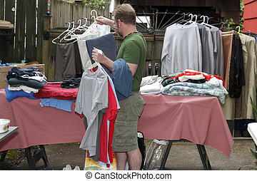 Man Holding Clothes at Sale - A caucasian man in short pants...