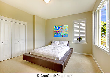 Bright bedroom with modern bed and art.