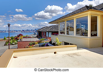 Modern house with patio and view of Seattle and water.
