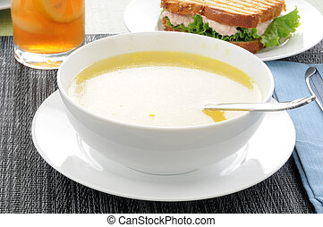 Soup and sandwich - A bowl of chicken noodle soup with a...