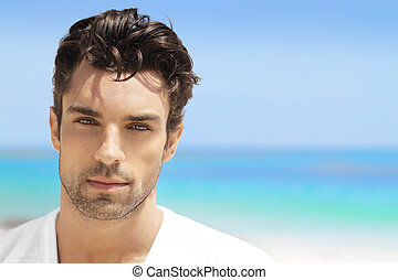 Handsome young man in casual white top against bright beach...