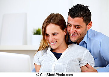 Lovely young couple browsing Internet on laptop - Portrait...