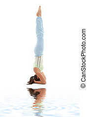 salamba sirsasana supported headstand on white sand - girl...