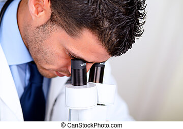 Professional medical man using a microscope