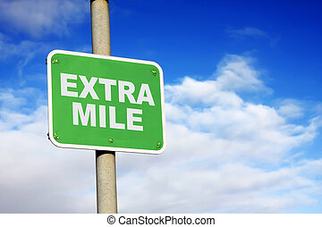 Green extra mile sign against a blue sky