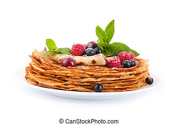 Pancakes with berries and mint on a white background