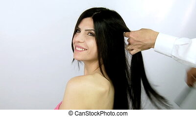 Woman getting hair ironed - Hairdresser straightening long...