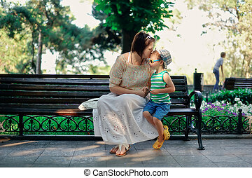 mother with the child - in park on a bench sit and talk...