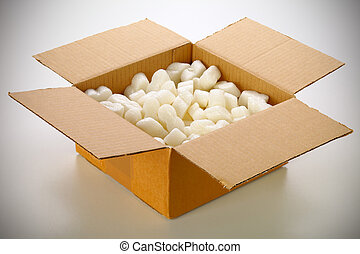 A cardboard box with yellow packing styrofoam peanuts,...