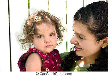 Big Sister - a young latino girl holding a little girl