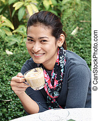 Asian woman holding a cup of tea or coffee and smiling