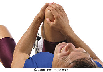 Knee injury - Male athlete lying on floor while clutching...