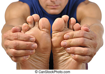 Hamstrings stretch - Closeup of bottom of bare feet of male...