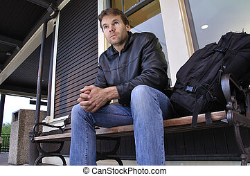 Traveler - Traveling man with backpack waits on bench for...