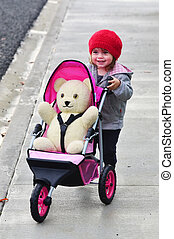 Little girl with teddy bear in stroller on the street