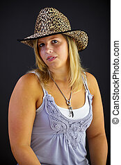 Young blond woman with hat on black background, studio shot. Adobe RGB