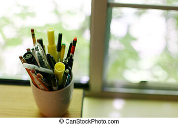 cup of pens and pencils - indoor close-up of cup of pens and...