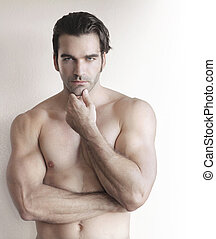 Handsome man - Shirtless young man with hand to chin against...