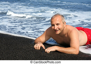 Black sand beach - Mature man on a black sand beach on Big...