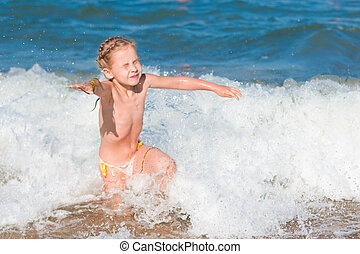 Little girl crying in the spray of waves at sea