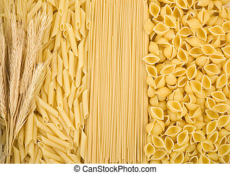 raw pasta and ear of wheat as background
