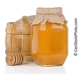 glass and wooden jars full of honey isolated on white...
