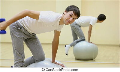 man engaged in a gym with a ball