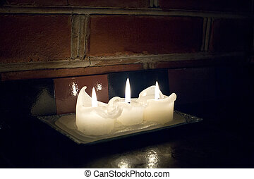 Three small candles lighted on fireplace shelf - Three small...