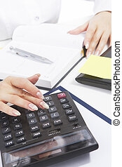 hands of white caucasian woman working with calculator using...